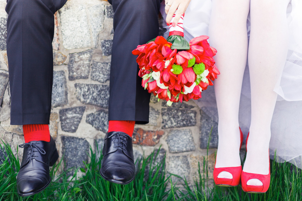 bride and groom with red shoes and socks and a bouqet of red flowers