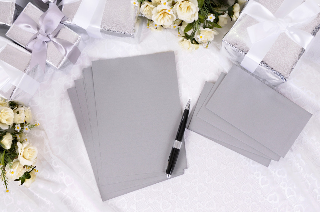 Silver gray writing paper or invitations with envelopes laid on bridal lace with several wedding gifts and white rose bouquets. Space for copy.